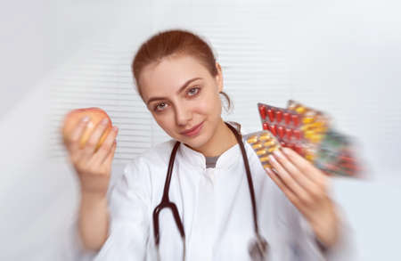 selectively: Portrait of a smiling young female doctor in white coat holding apple in one hand and pills in the other. This image is selectively blurred and toned. Stock Photo