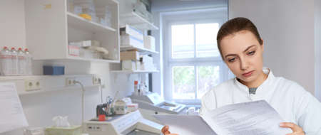 Panoramic image of a young female scientist reading printed notes in scientific laboratory