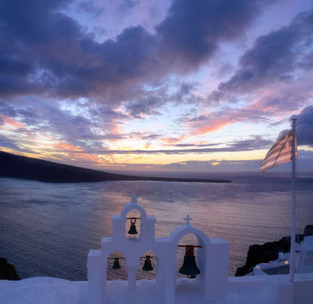 Greek flag on a local chapel in Oia village, Santorini island in Greece on a sunset