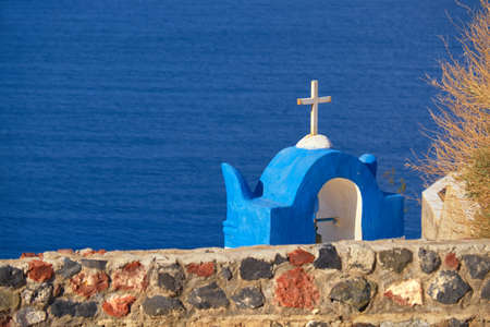 Cross of local chapel in Santorini Island in Greece over blue waters of caldera, text space. Shallow DOF, focus on the cross. Stock Photo