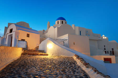Local church with blue cupola in Oia village, Santorini island, Greece in the evening