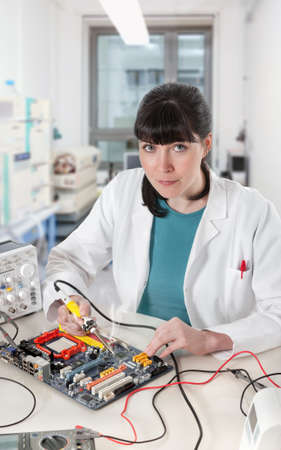 Young female tech soldering a circuit board in modern laboratory looks at the viewer photo