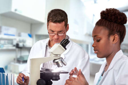 Scientists, senior Caucasian male and young African female, work with a microscope in research facility. Shallow DOF, focus on the mans eyes. Stock Photo