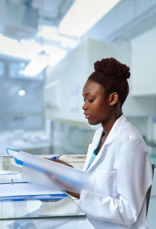 Biopsia: cheques biólogo resultados de la secuenciación afroamericanos en el laboratorio o centro de investigación científica. Centrarse en la cara y en las pestañas.