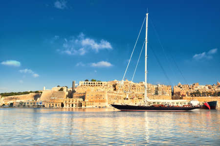 Sailing ship enters Grand Valetta bay with a view over Valettas traditional architecture on a bright day. This picture is toned. Stock Photo