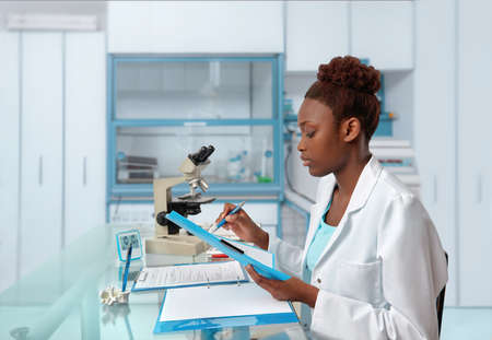 trial indoor: African-american biologist checks records in scientific lab or research facility. Focus on the face and eyelashes.