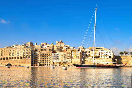 Sailing ship enters Grand Valetta Bay, Malta, with a view over Senglea traditional architecture on a bright day