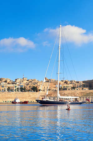 Sailing ship enters Grand Valetta bay with a view over Valettas traditional architecture on a bright day
