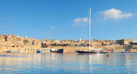 Sailing ship enters Grand Valetta bay with a view over Valettas traditional architecture on a bright day. Panoramic image. Stock Photo