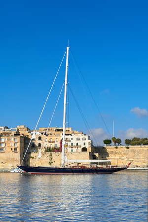 Sailing ship enters Grand Valetta bay with a view over Senglea traditional architecture on a bright day Stock Photo