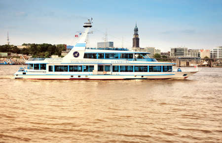 elba: HAMBURG, GERMANY- AUGUST 12, 2015: Boat with tourists goes on Elbe river in Hamburg with St. Michael church spire visible.