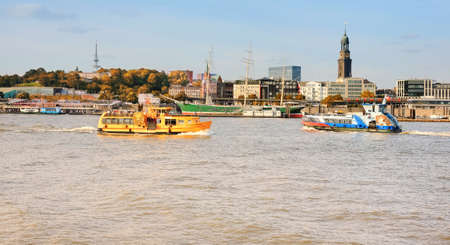 elba: HA�BURG, GERMANY- AUGUST 12, 2015: Boat with tourists goes on Elbe river in Hamburg with St. Michael church spire visible.