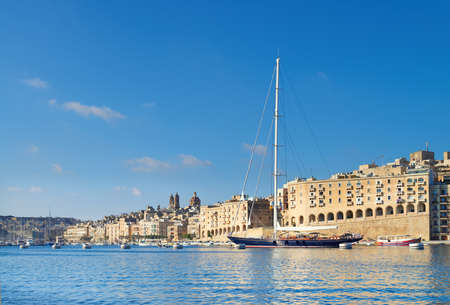 VALETTA, MALTA - JULY 25, 2015: Sailing ship enters Grand Valetta bay on a bright day in Summer, a small motor boat on the foreground