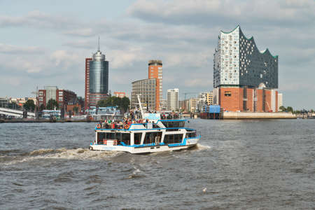 HANBURG, GERMANY- AUGUST 12, 2015: Boat with tourists goes on Elbe river towards Elbphilharmonie, a concert hall in the Hafen City quarter of Hamburg