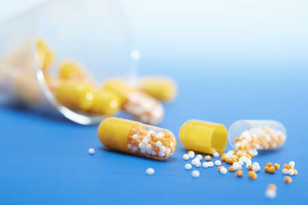 Split-open yellow capsule on blue gradient background, more capsules behing, text space