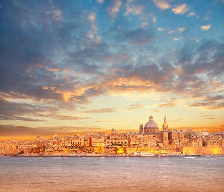 Mooie spitsen en kathedraalkoepel van Valletta onder dramatische hemel op de zonsondergang. Valletta, hoofdstad van Malta.