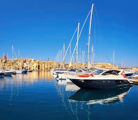 dwelling: Sailing boats on Senglea marina in Grand Bay, Valetta, Malta, on golden morning
