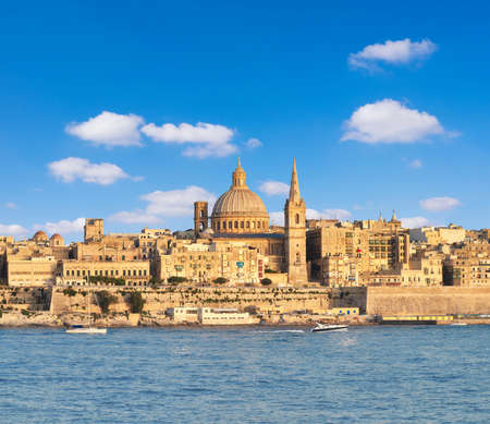 Malta, Valetta, cityscape. Touristic boat, ancient fortifications of La Valetta, old houses and St. Pauls Cathedral