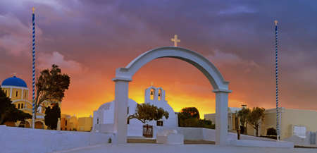 Arch, church and bell towers in Oia village, Santorini island, Greece on a sunrise with dramatic sky Stock Photo