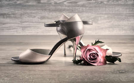 Argentine tango shoes with a rose on wooden floor Stock Photo