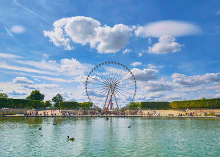 Ferris wheel on the Place de la Concorde from the Tuileries Garden in Paris, France, view from across the fountain, panoramic image.