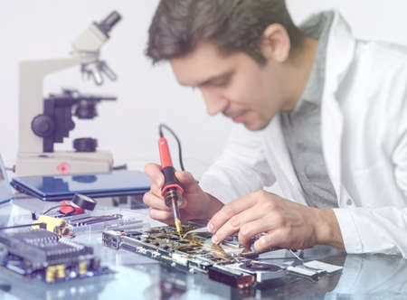 Electronics background. Young energetic male tech or engineer repairs electronic equipment in research facility. Shallow DOF, focus on the hands of the worker. This image is toned.