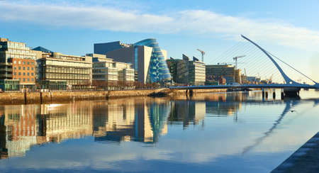 Modern buildings and offices on Liffey river in Dublin on a bright sunny day. Bridge on the right is a famous Harp bridge.