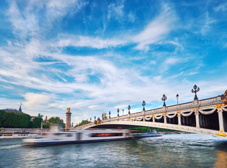 Ship passing under Alexandre III Bridge in Paris, long exposure to emphasize the movement. This image is toned.