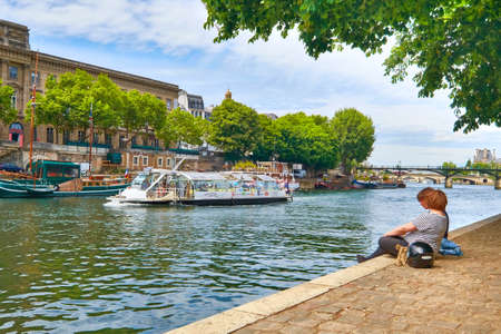 ile de la cite: PARIS, FRANCE - MAY 15, 2017: Young people sitting by the Seine river at the tip of Ile de la Cite island as passenger ships pass them by. Paris is the top touristic destination in Europe.