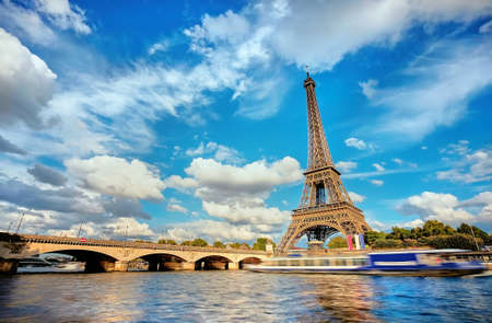 Cityscape of Paris with the Eiffel tower on a sunny day, long exposure to show motion of touristic boats