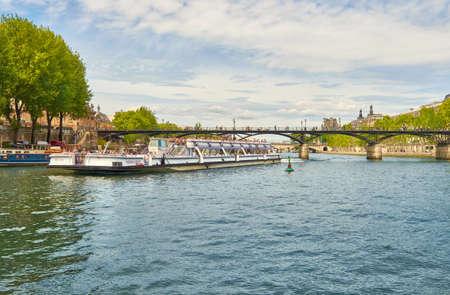 PARIS, FRANCE - MAY 15, 2017: Touristic boat passes below Pont des Arts on Seine river in Paris. Paris is the top touristic destination in Europe.