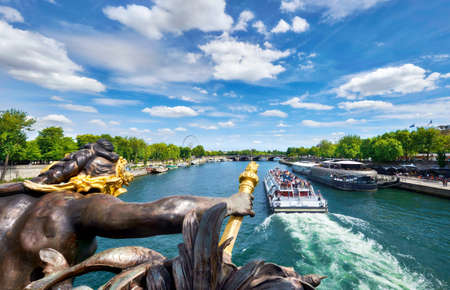 View of passenger boat from Alexander III bridge (pont Alexandre III) in Paris, France, on a bright day in Spring Stock Photo