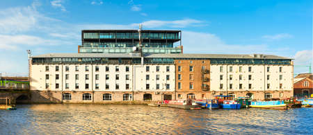 Refurbished part of Dublin Docklands or Silicon Docks on a bright morning. Longboats mooded in annex of Grand Canal. Panoramic image. Stock Photo