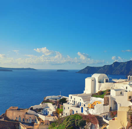 Beautiful Santorini in Greece - apartments and houses overlooking volcanic caldera in Oia village, toned panoramic image