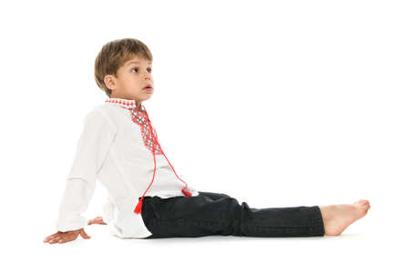 Little boy in Ukrainian embroidered shirt sitting down on white background