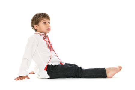 Weinig jongen in Oekraïense geborduurde overhemdszitting neer op witte achtergrond