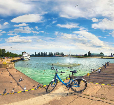 Panoramic view from promenade in Swinoujscie, Poland, with blue bike at the front. Toned image. Stock Photo