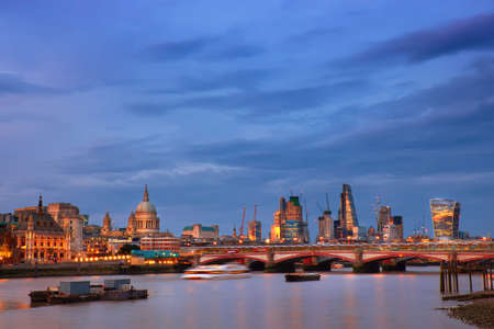 Illuminated London, view over Thames river from Waterloo bridge in the evening. This image is toned. Stock Photo