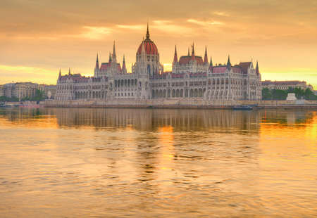 window view: Parliament building in Budapest, Hungary, on a golden sunrise with reflection in the river