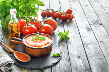 Tomato cream soup in a dark ceramic bowl served with cream and basil, text space Stock Photo