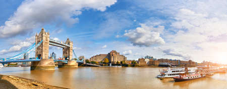 Panoramic image of Tower Bridge in London on a bright sunny day in Autumn with clouds