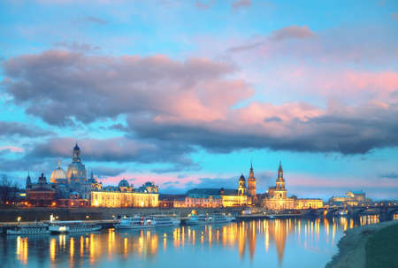 Night panorama of Dresden Old town with reflections in Elbe river and passenger ships