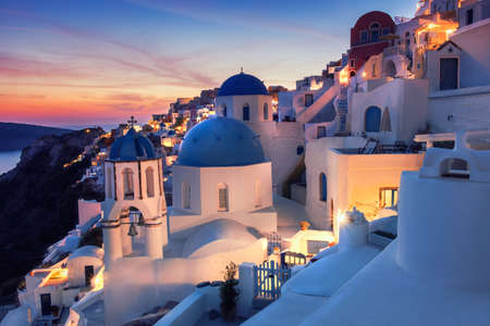 Oia village, Santorini island, Greece on a sunrise with local church overlooking famous volcanic caldera. Panoramic toned image, space for your text.