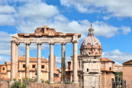 Ruins of the Roman Forum with the Temple of Saturn and the church of Santi Luca e Martina in Rome, Italy. Stock Photo