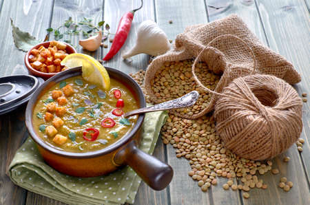 Spicy lentil soup with chili, garlic and onion, served with chili, lemon, croutons and thyme leaves in popttery ceramic bowl on the wooden table, with ingredients around the bowl Stock Photo