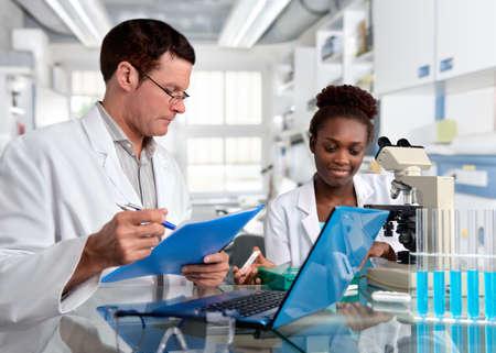Biopsia: Los científicos, mujeres caucásicas de alto rango y mujeres jóvenes de África, trabajan con un microscopio en una instalación de investigación. Shallow DOF, se centran en la cara de la niña.