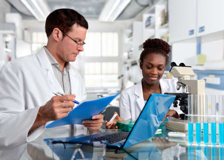 Wissenschaftler, älterer kaukasischer Mann und junge afrikanische Frau, arbeiten mit einem Mikroskop in der Forschungsanlage. Shallow DOF, konzentrieren sich auf das Gesicht des Mädchens. Standard-Bild