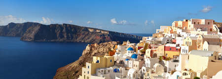 Panoramic image of Oia village, Santorini island, Greece, with local church and traditional appartments on a bright day Stock Photo