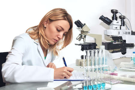 Young female scientist or tech writes down results of microsopic observations in research lab