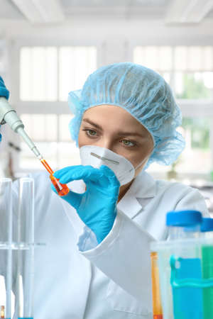 Young female tech or scientist loads liquid sample into test tube with plastic pipette. Shallow DOF, focus on the eyes and hand.